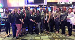 Guests gather for group photo in casino before slot tournament.