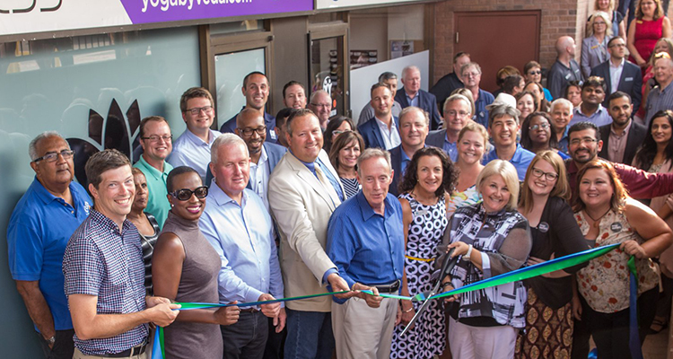 Members and staff pose for ribbon cuttting in front of new Chamber office.