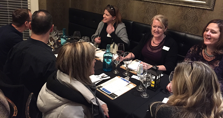 Members have conversation around table at restaurant.