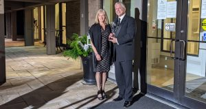 Terry Johnston and wife Susan pose with Peter Perry Award outside on front steps of Deer Creek Golf & Banquet Facility
