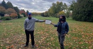Lorna McGhee presents Dave Paterson a certificate outside on the greens of Royal Ashburn Golf Course