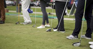 Golfers feet and clubs.